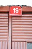 在一块红色板材的房子号码19 库存照片