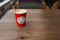 在一块红色纸玻璃的热奶咖啡与正面微笑 街道咖啡 库存照片