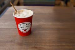 在一块红色纸玻璃的热奶咖啡与正面微笑 街道咖啡 免版税库存图片