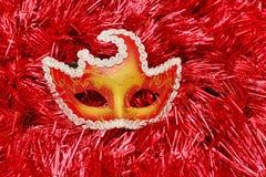 在一块红色背景圣诞节树闪亮金属片的明亮的色的面具与自由空间 免版税库存图片