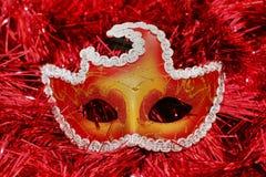 在一块红色背景圣诞节树闪亮金属片的明亮的色的面具 库存图片