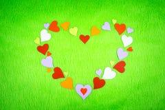在一块绿色布料的色纸心脏 免版税库存图片