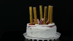 在一块美丽的时髦的甜新鲜的白蛋糕的蜡烛用用在上面的奶油和椰子剥落装饰的樱桃果酱 股票录像