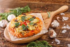 在一块美丽的木匾的一个可爱的矮小的可口薄饼归档的在一张木桌上 自创薄饼用乳酪和vegetabl 免版税库存图片