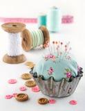 在一块老金属杯形蛋糕的花卉针垫 库存图片