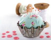 在一块老金属杯形蛋糕的针垫 免版税库存照片
