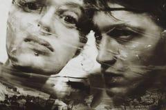 在一块肮脏的泥泞的玻璃的男人的和妇女的面孔 库存照片