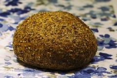 在一块自然蓝色纺织品餐巾的黑麦面包谎言,健康食品的概念大面包  免版税图库摄影