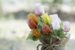 在一块花瓶麻袋布的人为玫瑰在被弄脏的背景 免版税库存图片