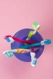 在一块蓝色塑料玻璃的牙刷在桃红色背景 库存照片