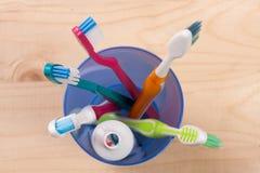 在一块蓝色塑料玻璃的牙刷在轻的木背景,顶视图 免版税库存图片