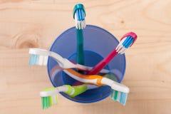 在一块蓝色塑料玻璃的牙刷在轻的木背景 免版税库存图片