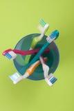 在一块蓝色塑料玻璃的牙刷在绿色背景 免版税库存照片