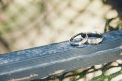 在一块蓝色木头的结婚戒指 图库摄影