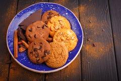 在一块蓝色板材上是饼干、黑巧克力和一些根肉桂条 在一张木表 里面 在视图之上 免版税图库摄影