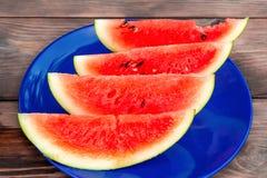 在一块蓝色板材的切的成熟红色西瓜在一张木桌上 库存照片