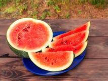 在一块蓝色板材的切的成熟红色西瓜在一张木桌上 图库摄影