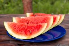 在一块蓝色板材的切的成熟红色西瓜在一张木桌上 免版税库存照片