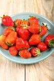 在一块蓝色板材的成熟草莓在木背景 库存图片