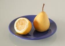 在一块蓝色板材的果子在灰色背景 免版税库存照片