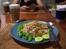 在一块蓝色板材的油煎的面条泰国样式在与i的一张棕色桌上 免版税库存图片