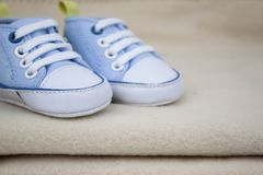 在一块蓬松毛巾的蓝色婴儿运动鞋 免版税图库摄影