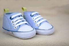 在一块蓬松毛巾的蓝色婴儿运动鞋 库存图片