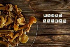 在一块透明板材的用卤汁泡的蘑菇在一张木桌上 与盘的名字的信件 库存图片