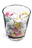 在一块透明玻璃的色的药片 免版税库存照片
