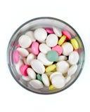 在一块透明玻璃,顶层的色的药片 免版税库存照片