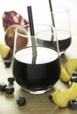 在一块透明美丽的玻璃的蓝莓汁用桃子和一片红色叶子 免版税库存图片