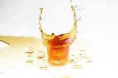 在一块透明玻璃和冰切片的威士忌酒飞溅在白色b 免版税库存图片
