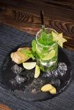 在一块透明玻璃的刷新的mojito鸡尾酒在木背景 夏天饮料 复制空间 免版税库存图片