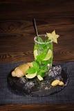 在一块透明玻璃的新鲜的夏天mojito鸡尾酒与在木桌上的一个长的茶匙 夏天饮料 复制空间 库存图片