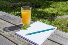 在一块透明玻璃的新鲜的橙汁在一张木桌上,薄荷叶,笔记薄,铅笔 库存照片