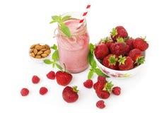 在一块金属螺盖玻璃瓶玻璃的桃红色草莓和莓圆滑的人与秸杆和疏散莓果 免版税库存照片
