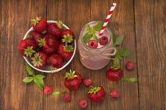 在一块金属螺盖玻璃瓶玻璃的桃红色草莓和莓圆滑的人与秸杆和疏散莓果 免版税图库摄影
