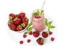 在一块金属螺盖玻璃瓶玻璃的桃红色草莓和莓圆滑的人与秸杆和疏散莓果 免版税库存图片