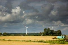 在一块金黄麦田的风轮机 免版税库存图片