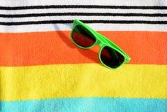 在一块镶边毛巾的太阳镜 库存图片