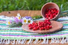 在一块镶边餐巾在美丽的花附近站立木碗和一个杯子用野草莓 库存图片
