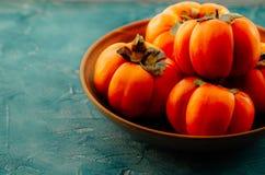 在一块陶瓷板材的成熟橙色柿子果子 柿子是钙的来源,钾,碳水化合物的来源 免版税库存照片