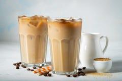 在一块高玻璃的冰冻咖啡与奶油倾吐了和咖啡豆 在浅兰的背景的冷的夏天饮料 库存照片