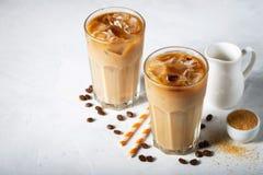 在一块高玻璃的冰冻咖啡与奶油倾吐了和咖啡豆 在浅兰的背景的冷的夏天饮料 免版税图库摄影