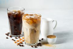 在一块高玻璃的冰冻咖啡与奶油倾吐了和咖啡豆 在浅兰的背景的冷的夏天饮料 免版税库存图片