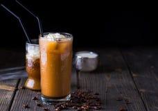 在一块高玻璃的冰冻咖啡在黑暗的自然书桌上 库存照片
