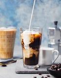 在一块高玻璃的冰冻咖啡与奶油倾吐了和咖啡豆 免版税库存图片