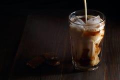 在一块高玻璃的被冰的咖啡与奶油倾吐了  库存图片