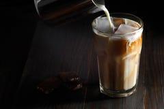 在一块高玻璃的被冰的咖啡与奶油倾吐了  免版税库存照片