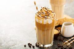 在一块高玻璃的被冰的焦糖拿铁咖啡 免版税库存照片